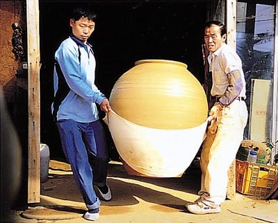 Ulsan Onggi potters carry a freshly made jar.